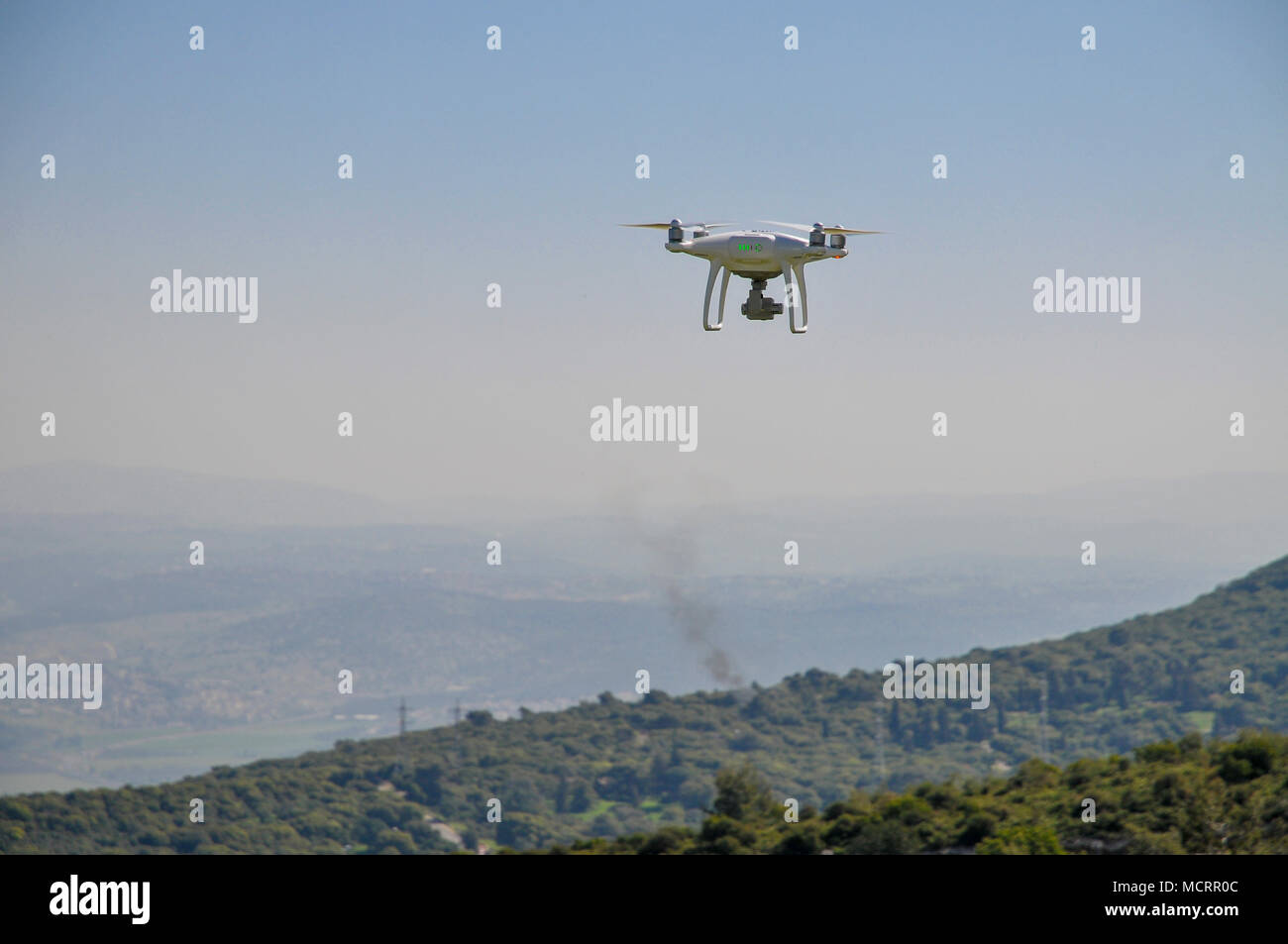 Remote control Quadrocopter, drone, with camera flying against a blue sky - Stock Image
