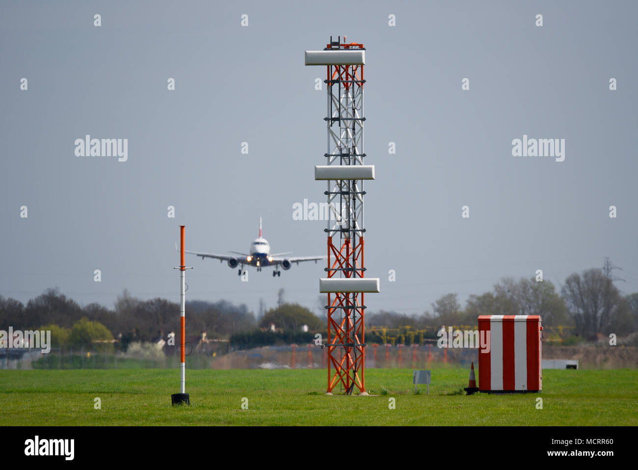 ILS Glide slope tower landing system at London Southend Airport. infrastructure. With British Airways Embraer jet plane side slipping in to land - Stock Image