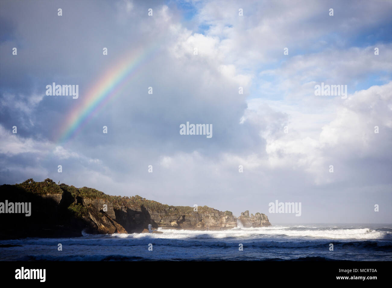 A rainbow shows over Dolomite Point at Punakaiki along the West Coast Region of the South Island, New Zealand. - Stock Image