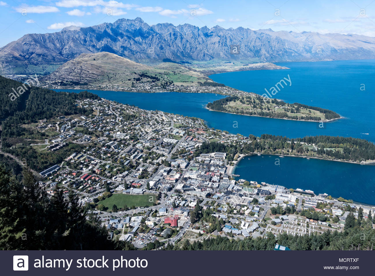 Queenstown sits on Lake Wakatipu with The Remarkables in the background, South Island, New Zealand. - Stock Image