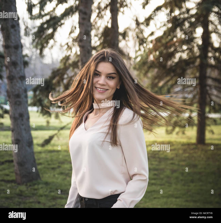 Svelte Girl in motion in the park smiling - Stock Image