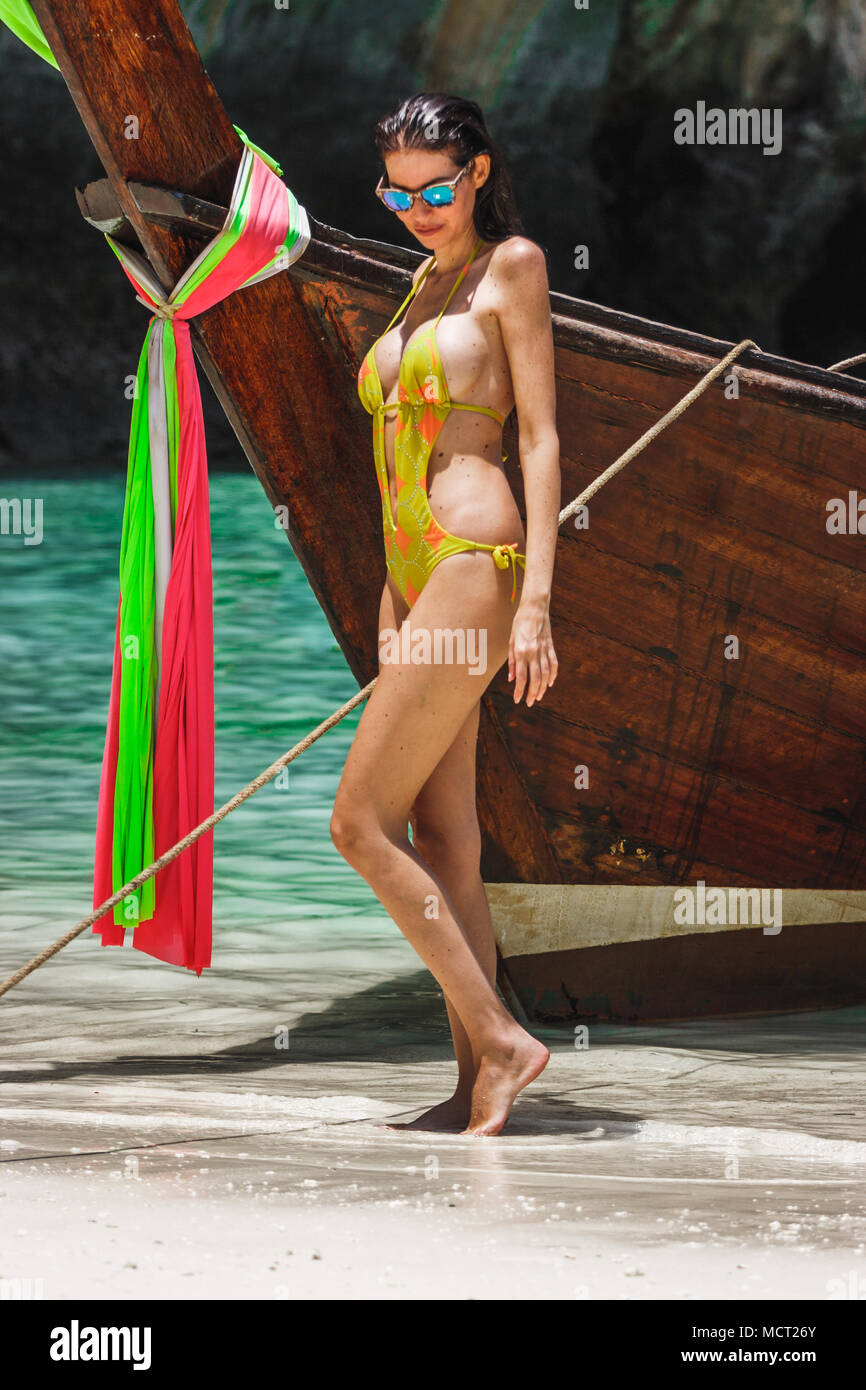 Picture of a woman model in a yellow bikini posing next to a thai long tail boat in Maya Bay, Phi Phi Leh, Thailand - Stock Image