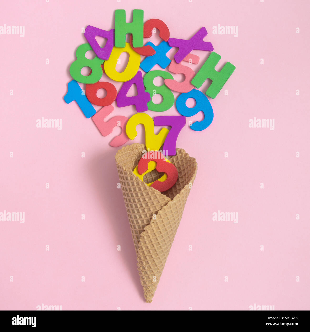 Ice cream cone with colorful wooden numbers and letters on pastel ...