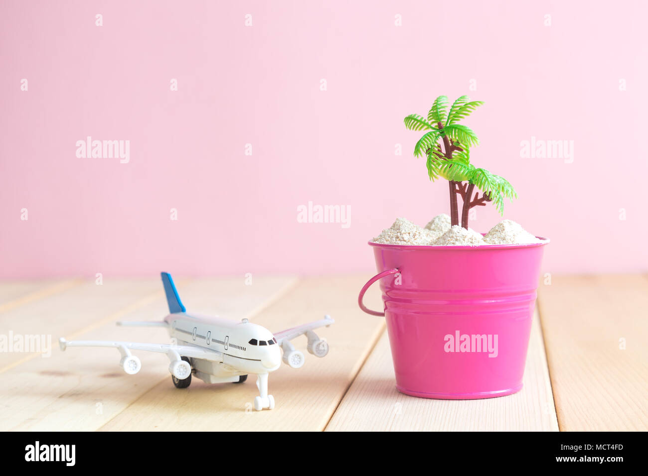 Airplane model toy and bucket full of sand with palm tree on table against pastel pink background minimal travel concept. Space for copy. Stock Photo