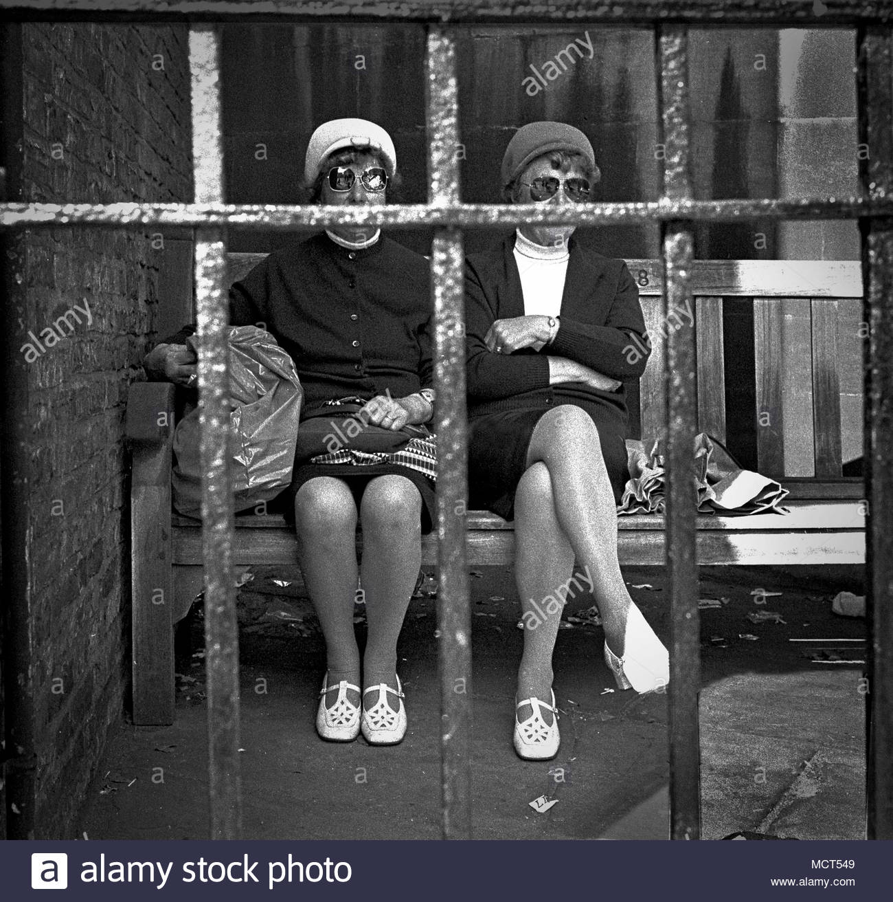 Two ladies (possibly sisters or twins) seated in a shady gated corner of York City Centre in Northern England, UK in  the 1970s. The females are wearing the same style of shoes and similar sunglasses.  photo DON TONGE photographer - Stock Image