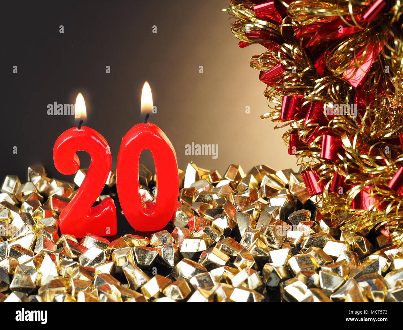 Birthday-anniversary candle showing Nr. 20  Lit red candle good for an anniversary or birthday background. - Stock Image