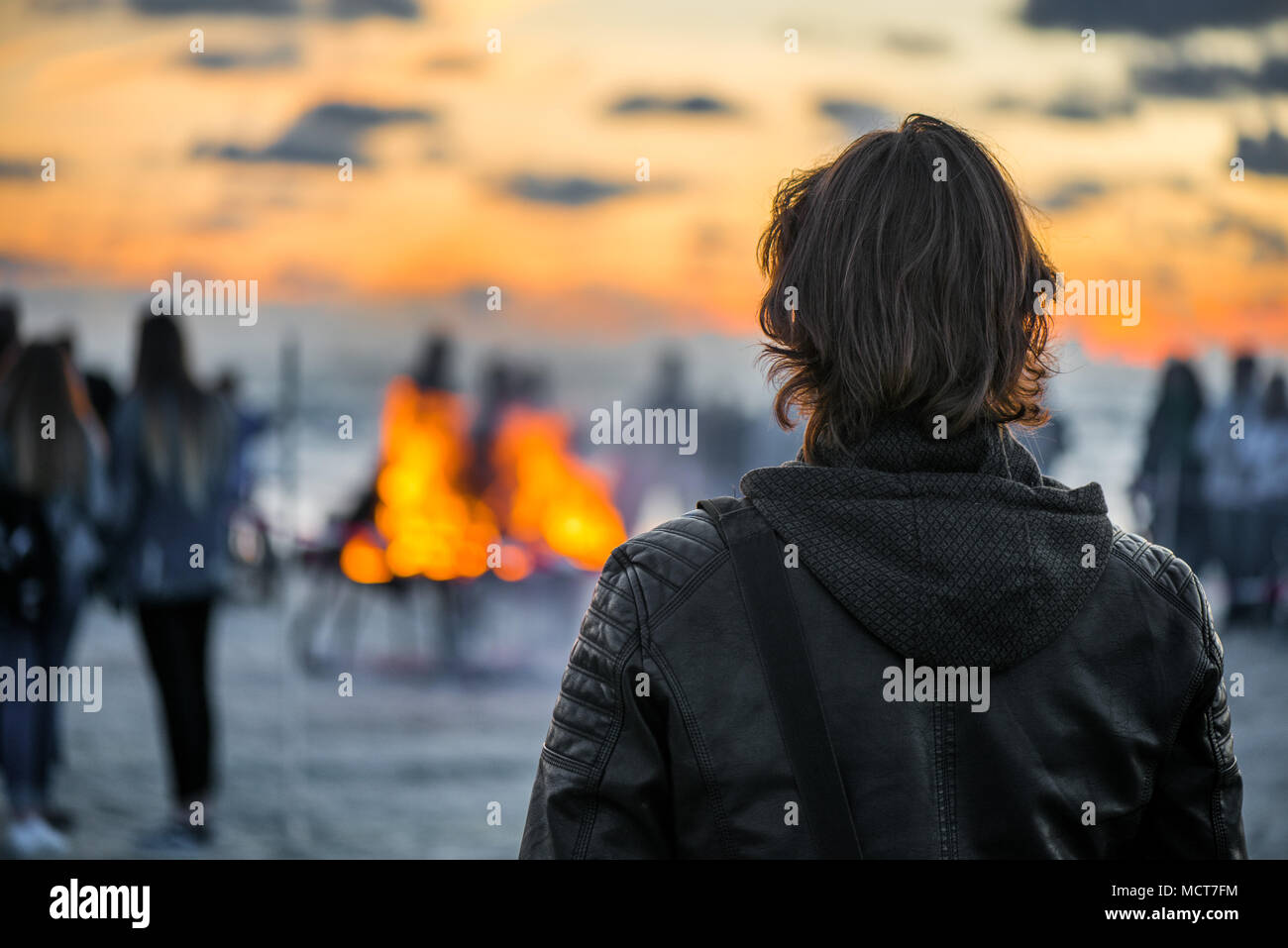 Lonely young man looking at the sunset and waiting his love. Romantic bonfire night at seaside. People gathering together to celebrate Night of ancien - Stock Image