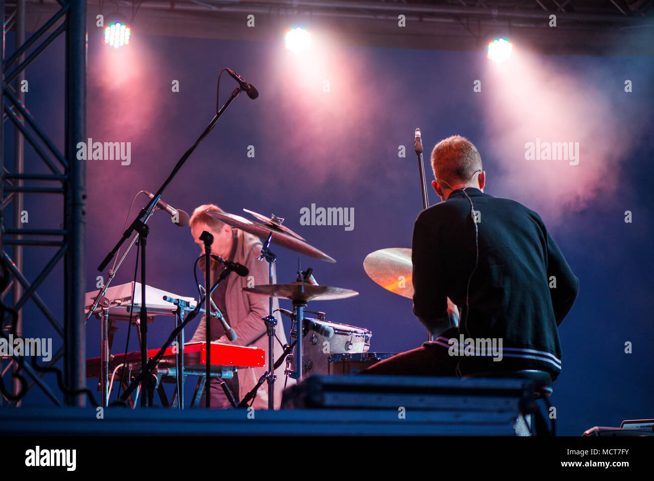 Shot of a man playing drums on stage during music festival in summer. Band performing their songs. Live concert of electronic music at night. Colorful - Stock Image