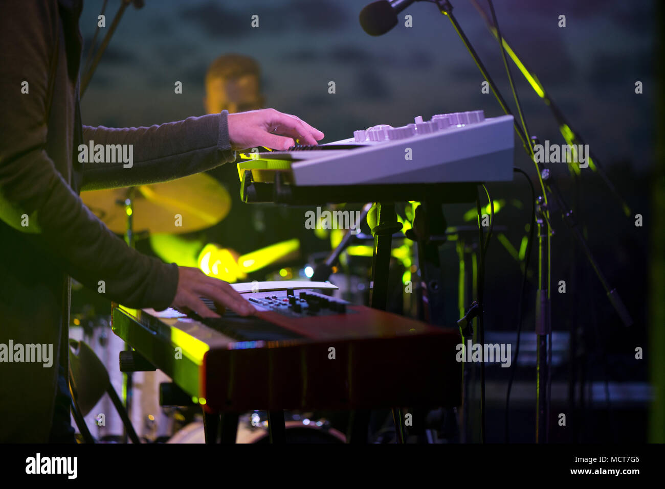 Male musician plays a musical instrument on the stage. Artist playing on the keyboard synthesizer piano keys. Live concert of electronic music at nigh - Stock Image
