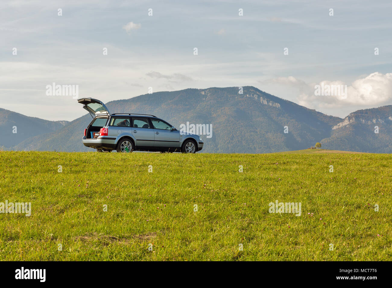 hatchback car with open trunk on the top of the summer hill. blue sky and mountains in the background. - Stock Image