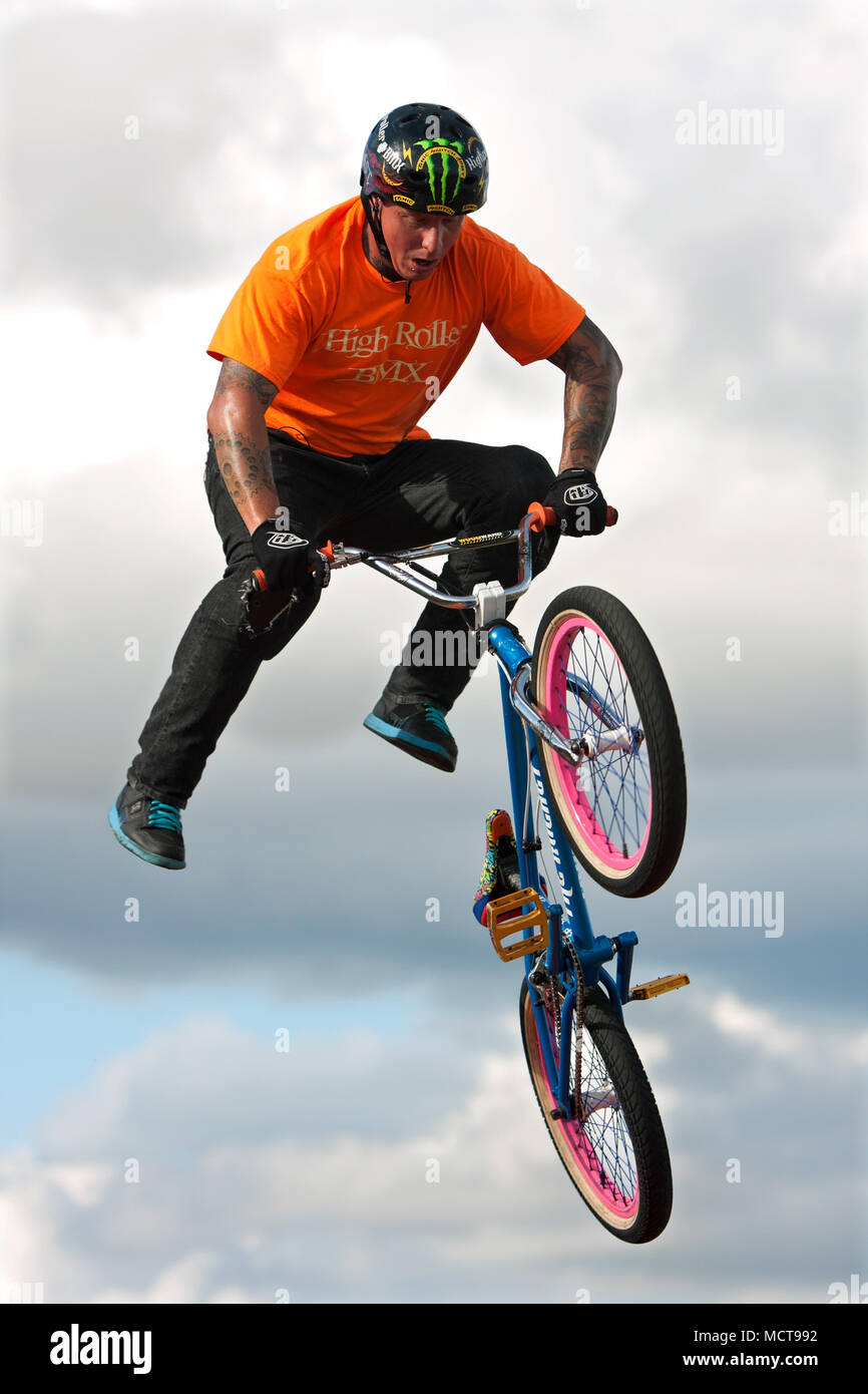 A young man with the High Roller BMX club rotates his bike in midair doing a BMX stunt at the Georgia State Fair on September 27, 2014 in Hampton, GA. - Stock Image