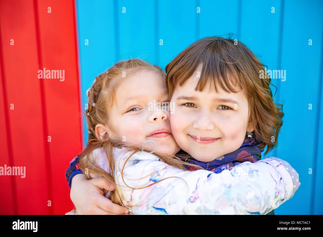 Happy little girlfriends embrace - Stock Image