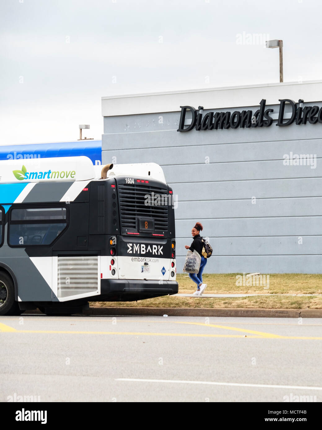 An African American woman prepairs to board an Oklahoma City bus in front of Diamonds Direct store. Oklahoma City, Oklahoma, USA. - Stock Image