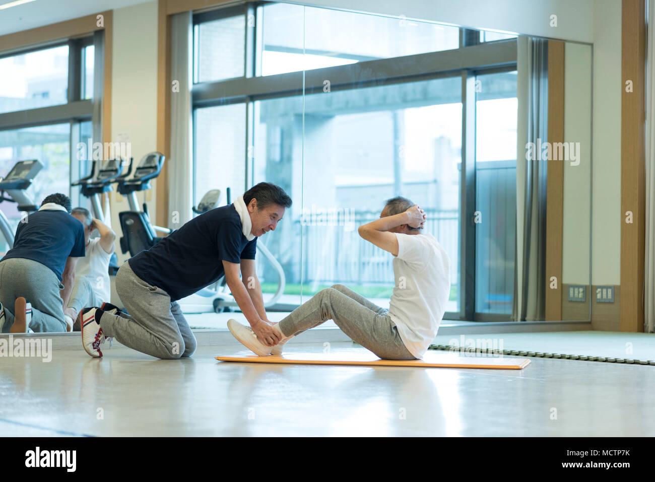 Senior man exercising stomach muscles - Stock Image