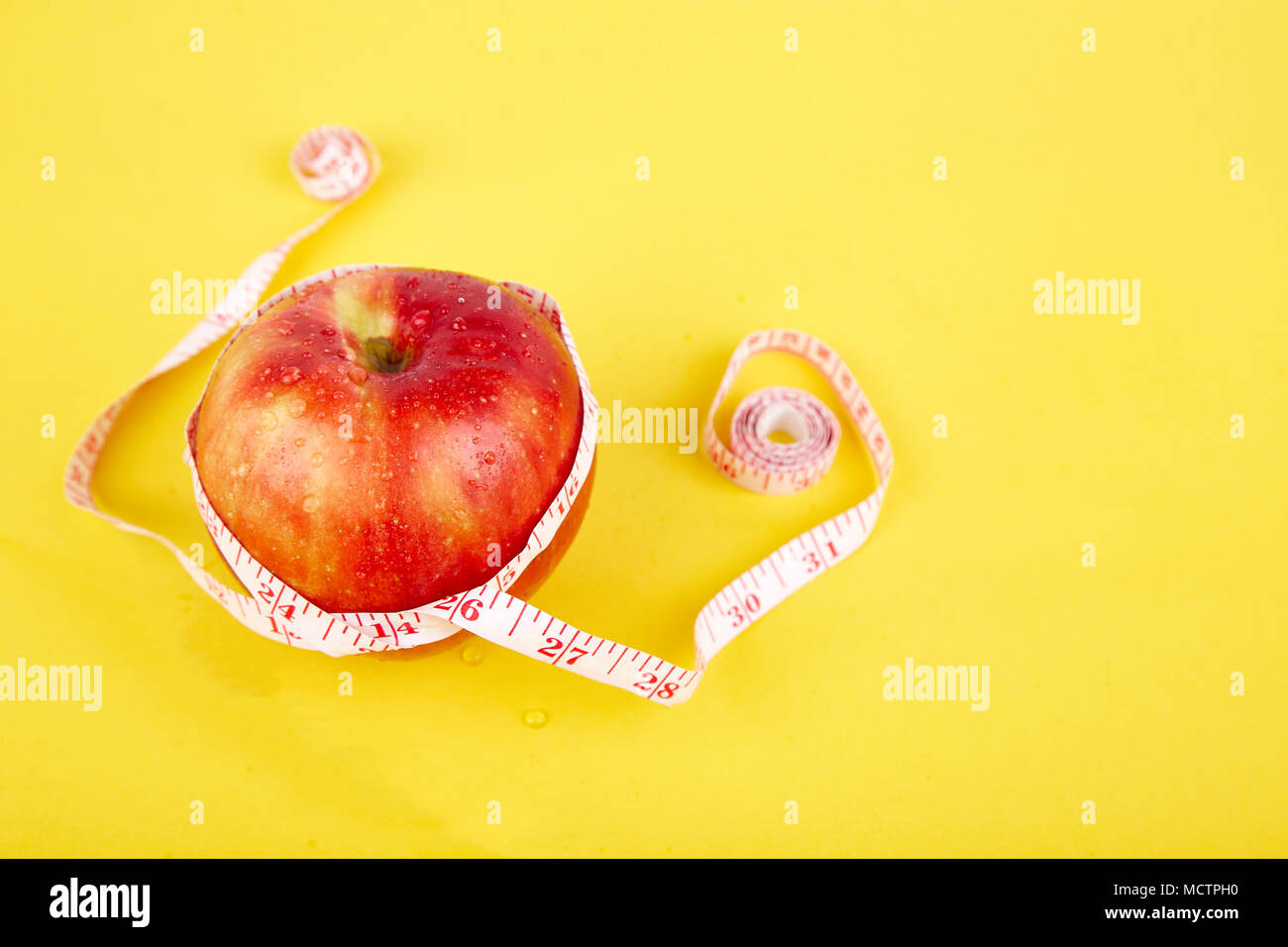Measuring tape wrapped around a red apple as a symbol of diet on yellow paper background. Weight loss concept. Diet. Dieting concept. Vegan. Clear foo - Stock Image