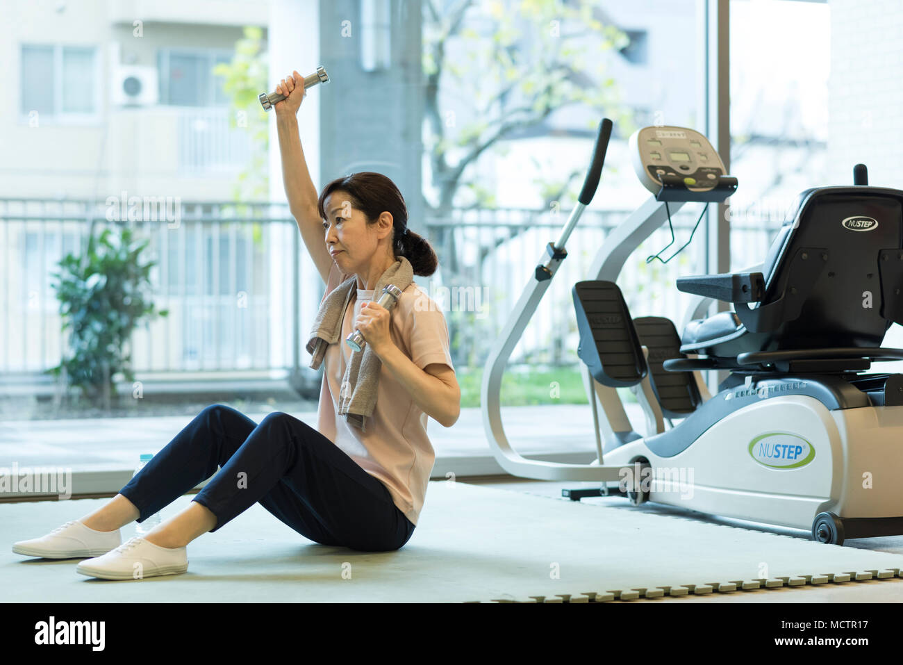 Senior woman working out with dumbbell - Stock Image