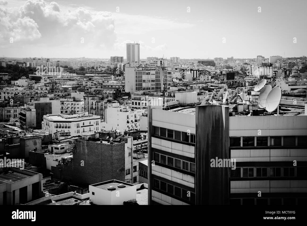 Old fashioned black and white picture of satellite dishes on a roof of a tall building in Casablanca, Morocco - Stock Image