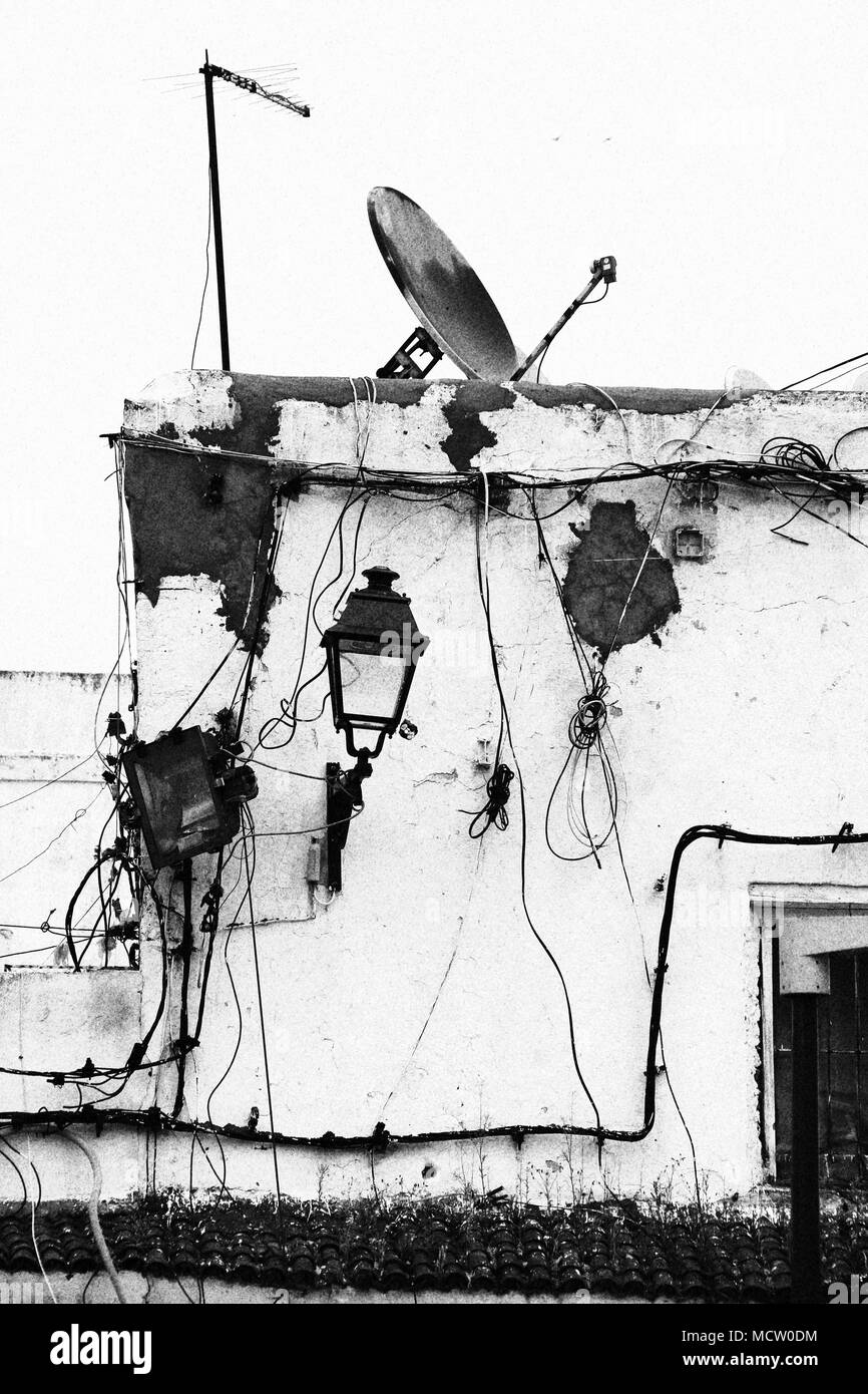 Old fashioned picture of a house facade with power lines, electrical installations and a satellite dish in Casablanca, Morocco - Stock Image