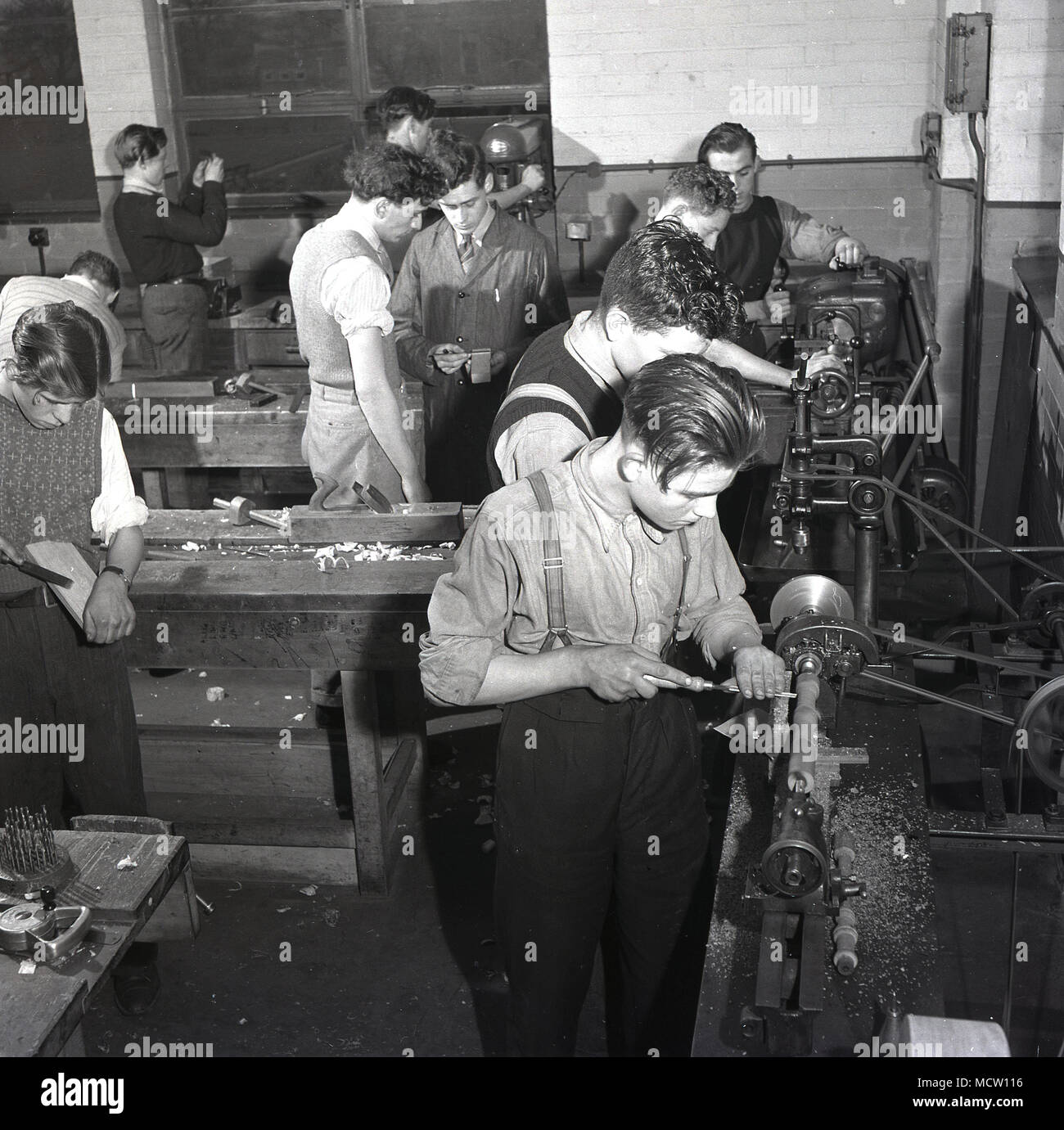 Historical picture, 1950s, of a group of male engineering apprentices using machine tools and getting 'hands on', practical experience in an industrial workshop, England, UK. In post-war Britain there was a major expansion of technical colleges and apprenticeship schemes to encourage more young people into important industrial sectors such as engineering and manufacturing. Stock Photo