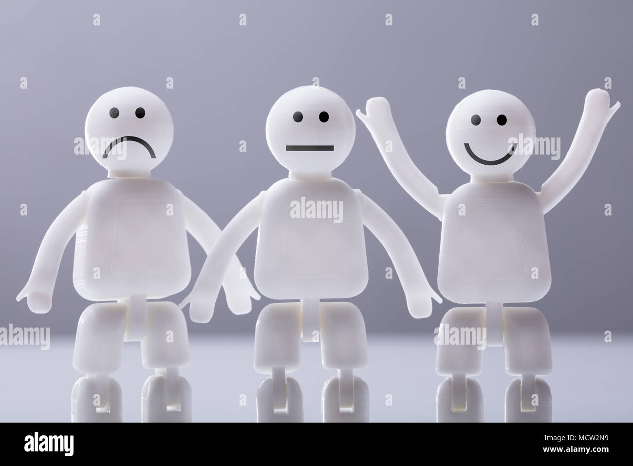 Close-up Of Three Human Figures Showing Various Facial Expressions Against Grey Background - Stock Image