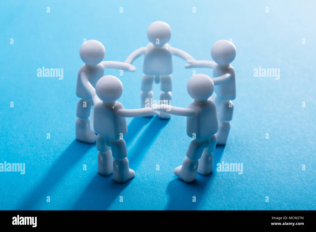 Close-up Of Human Figures Holding Their Hands Standing On Blue Background - Stock Image