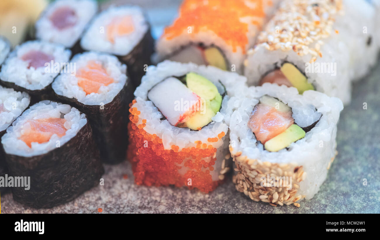 Sushi Take Away Box with Maki and Calofornia Rolls and Nigiri withSalmon and Tuna. Served in a takeaway Box with ginger and Wasabi. Sushi Set - Stock Image