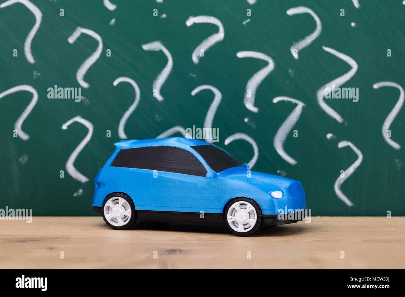 Close-up Of A Blue Car In Front Of Chalkboard Showing Question Mark Signs - Stock Image