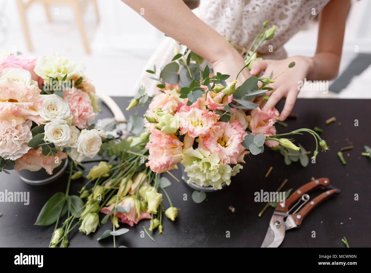 Master class on making bouquets for kids. Spring bouquet in metal ornamental flowerpot. Learning flower arranging, making beautiful bouquets with your own hands - Stock Image