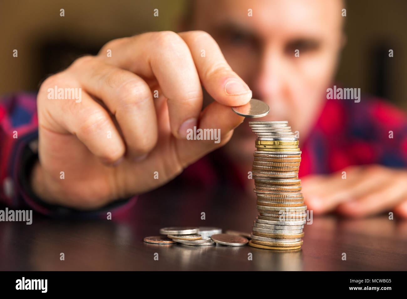 Unidentifiable man counts his coins on a table. Personal finance, finance management, thrifty or avarice concept. - Stock Image