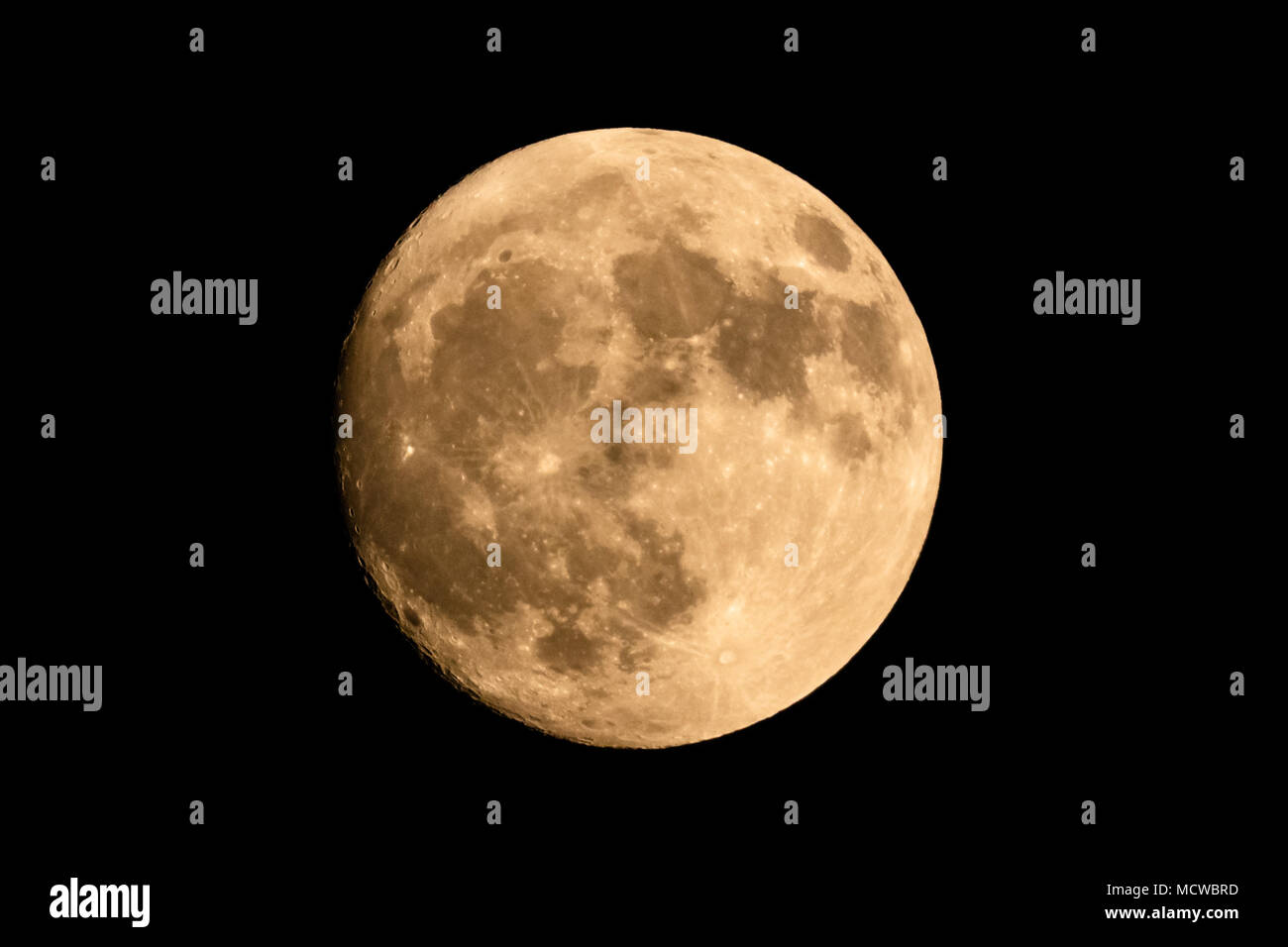 Closeup of a large shining full moon against dark background - Stock Image