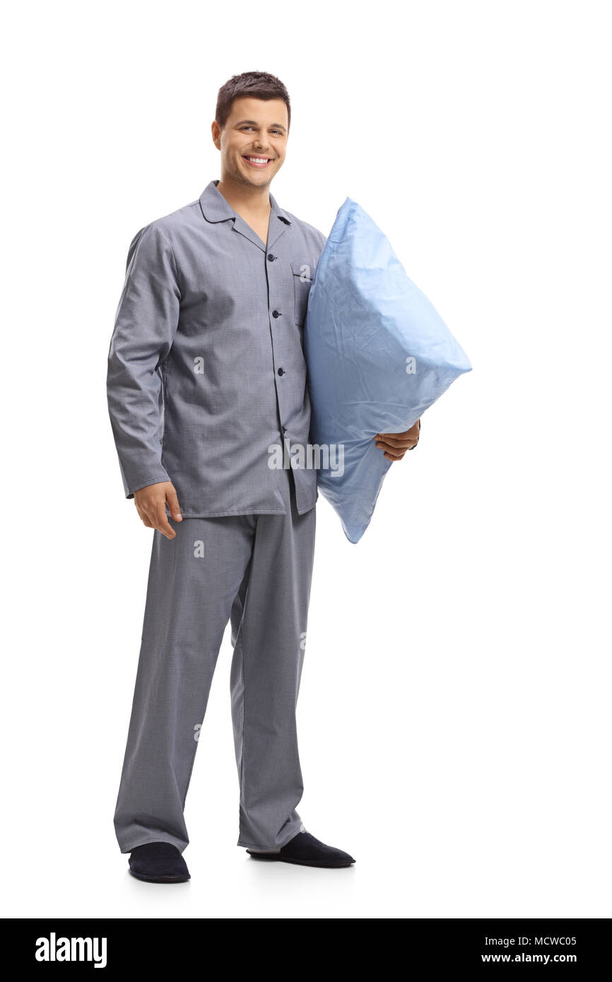 Full length portrait of a young man in pajamas holding a pillow isolated on white background - Stock Image