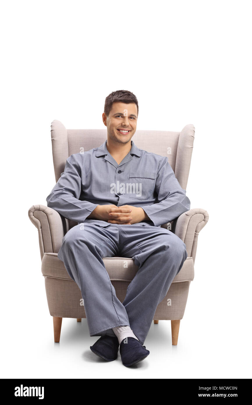 Young man in pajamas sitting in an armchair and looking at the camera isolated on white background - Stock Image