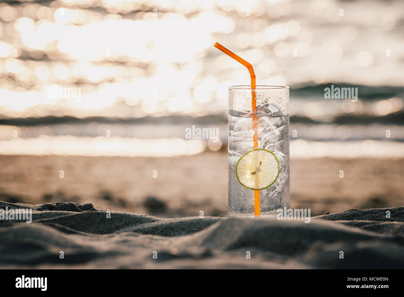 Picture of a glass of Gin Tonic with straw and lime slice on the beach, at sunset. Long Beach, Ko Lanta, Thailand. - Stock Image