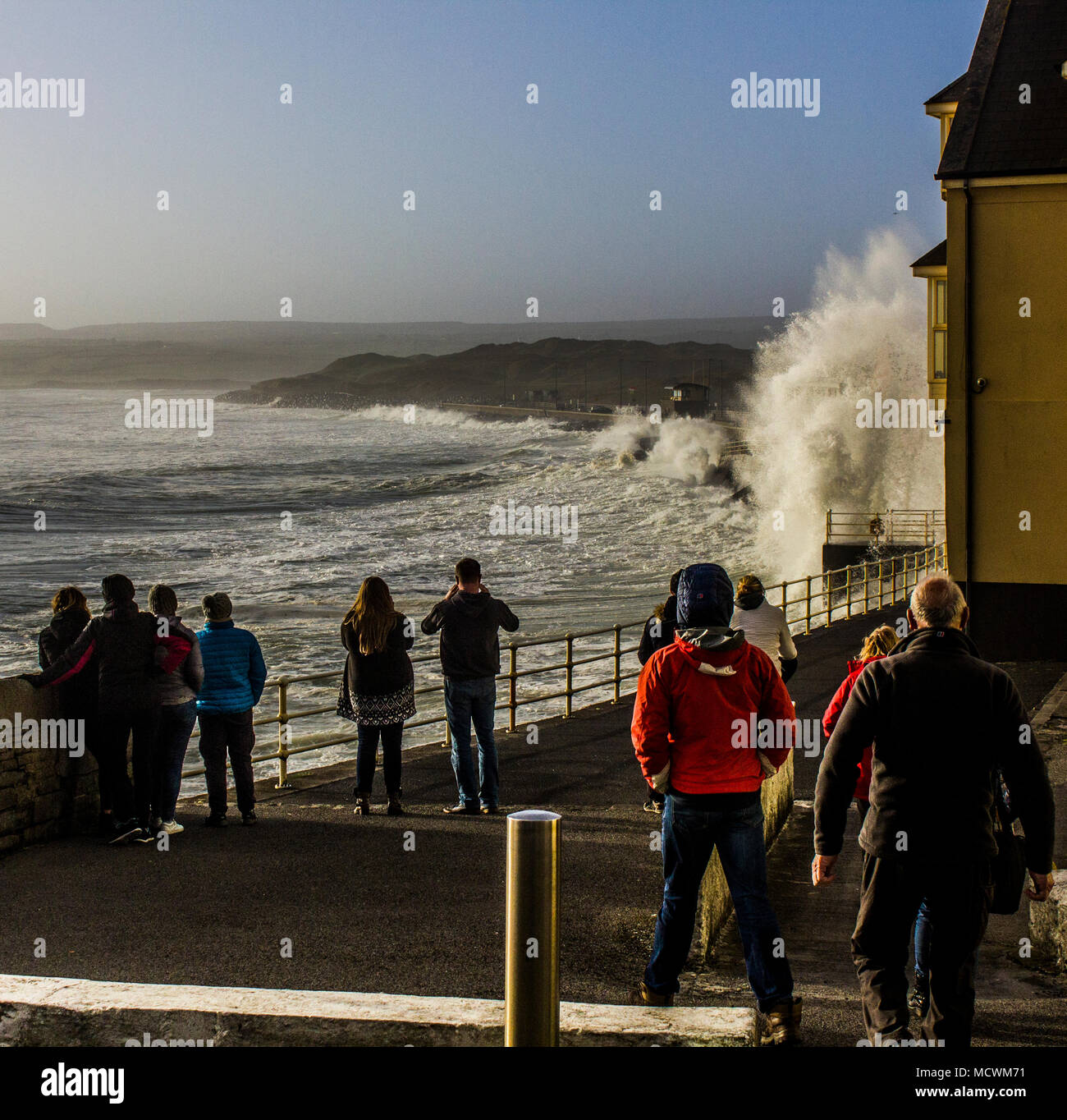 Crowd watching waves crashing over promenade in Lahinch at high tide - Stock Image