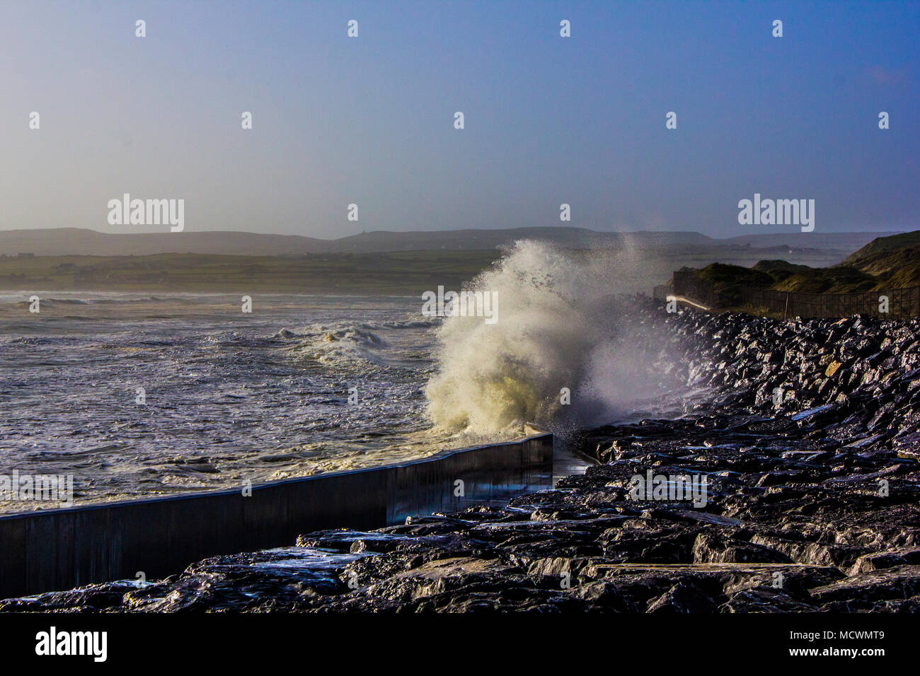 Wave crashing into wall at Lahinch beach during high tide - Stock Image