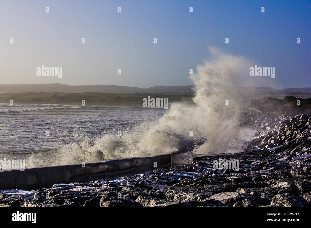 Wave crashing into wall at Lahinch beach during high tide causing big splash - Stock Image