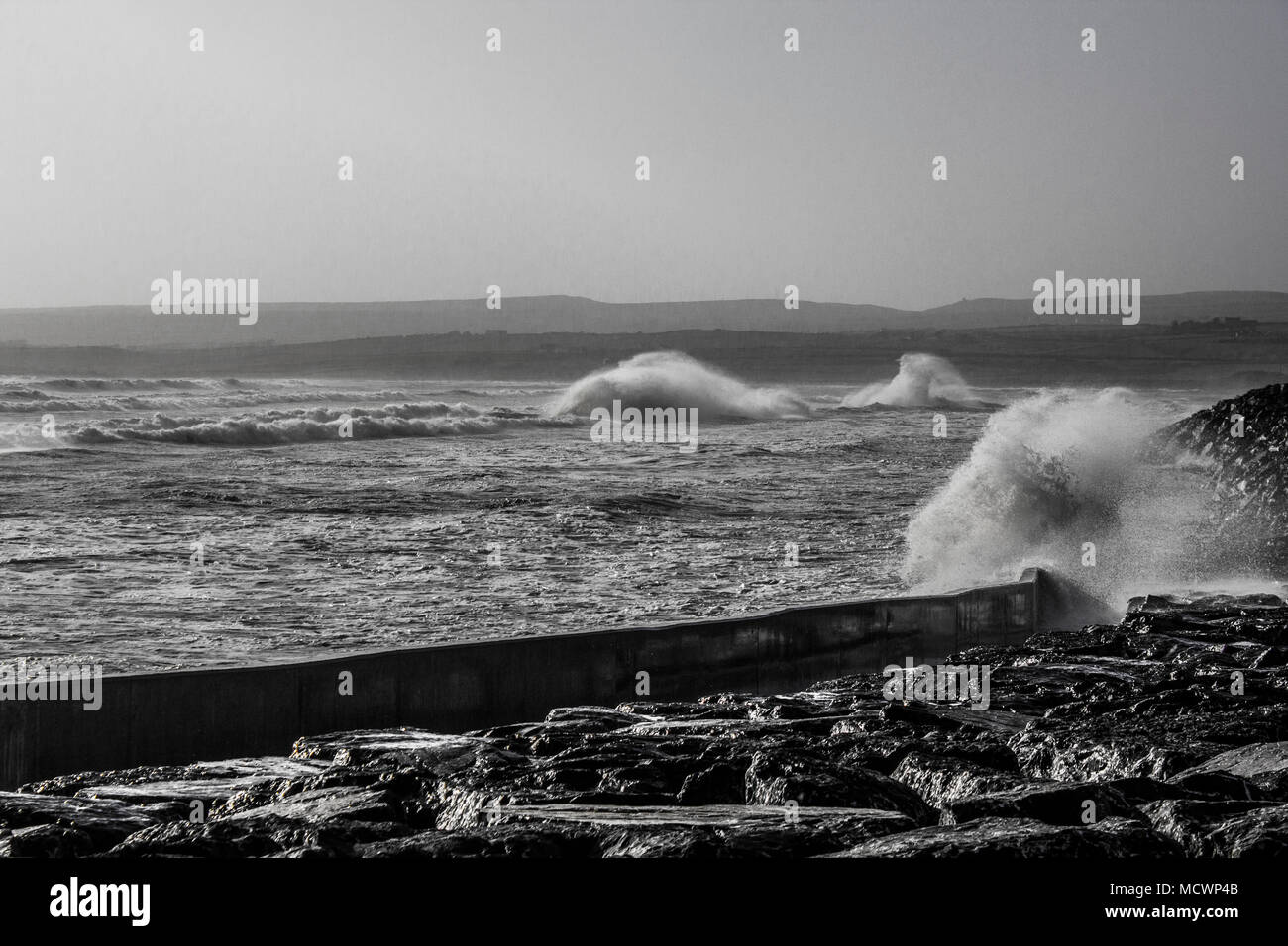 Waves crashing into wall at Lahinch beach during high tide black and white - Stock Image
