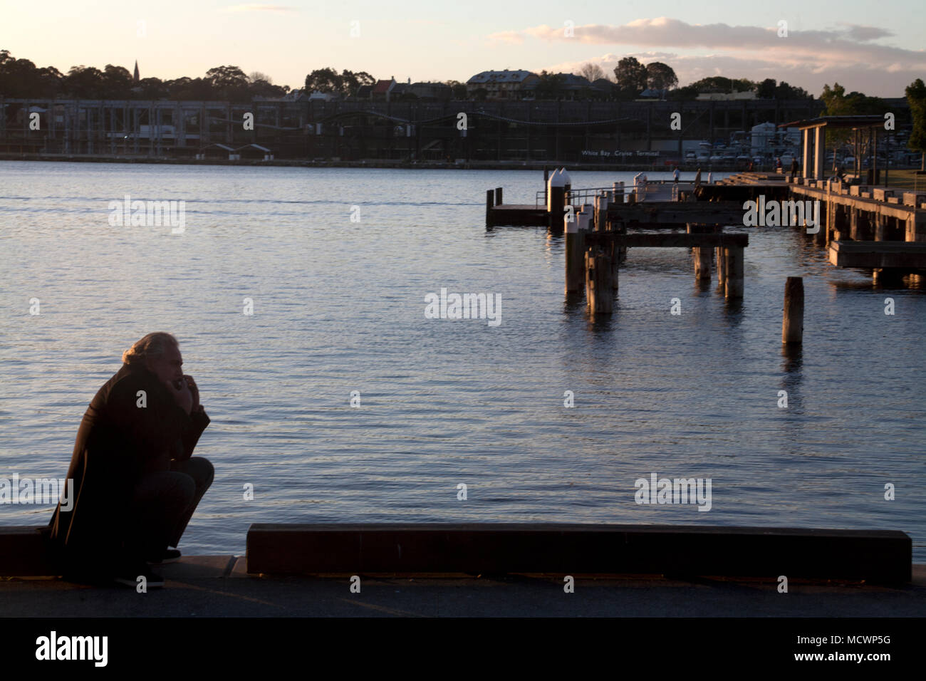 man squatting at sunset jones bay pyrmont sydney new south wales australia - Stock Image