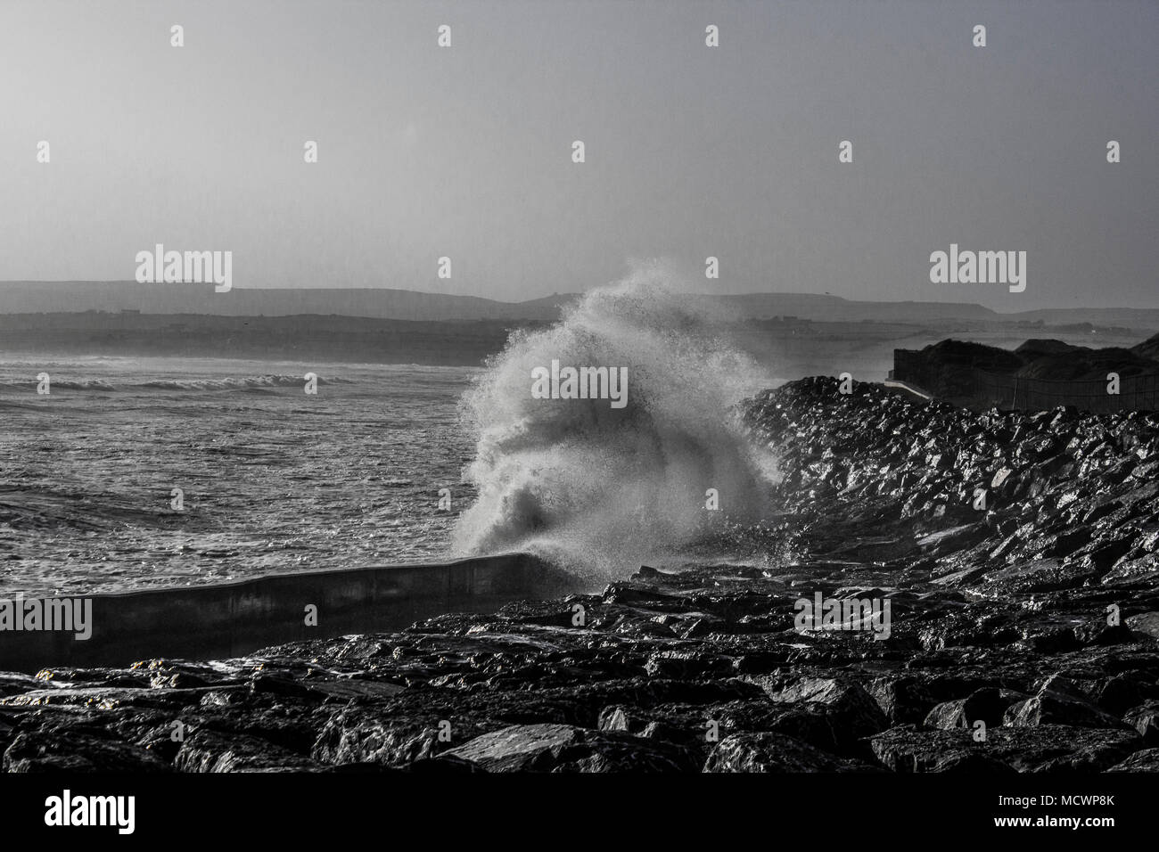 Wave crashing into wall at Lahinch beach during high tide black and white - Stock Image