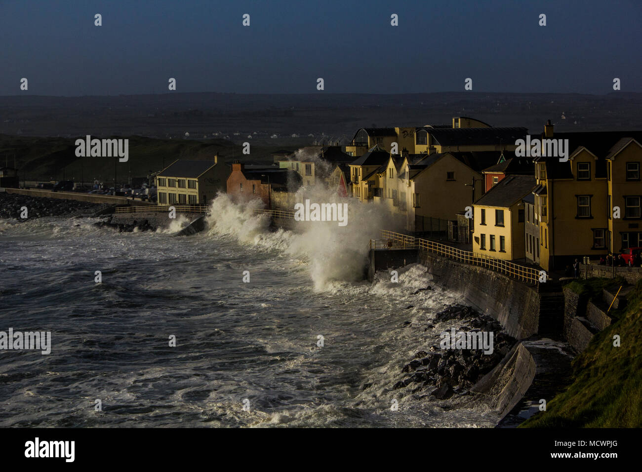 Lahinch seafront property and promenade getting hit by wave at high tide - Stock Image
