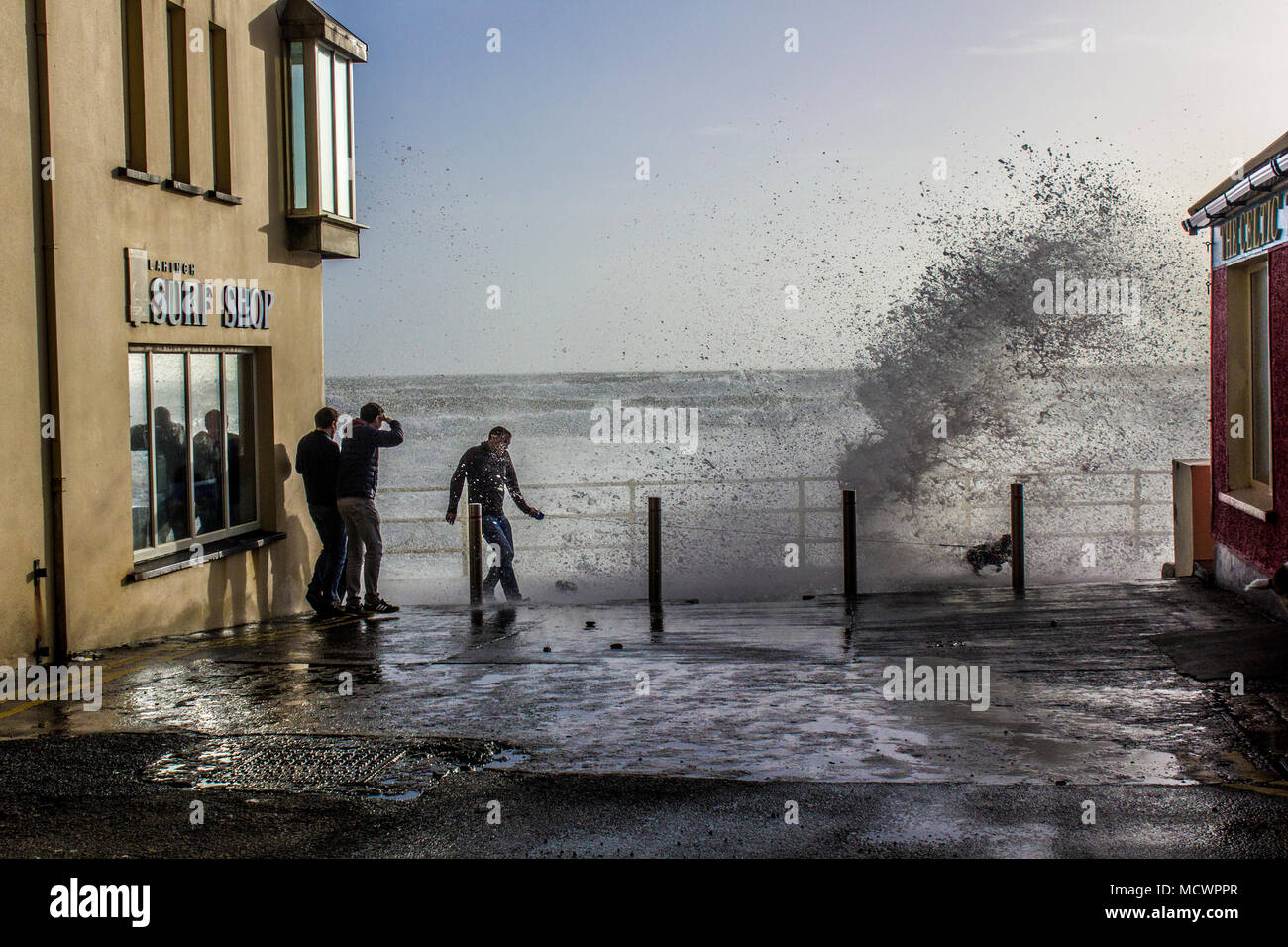 Man walking dog get hit by wave on the promenade in Lahinch - Stock Image