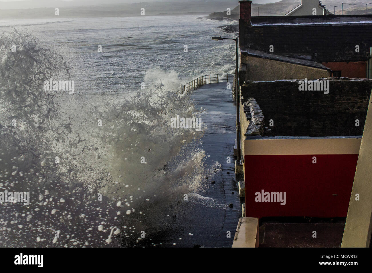 Wave coming over promenade in Lahinch at high tide - Stock Image