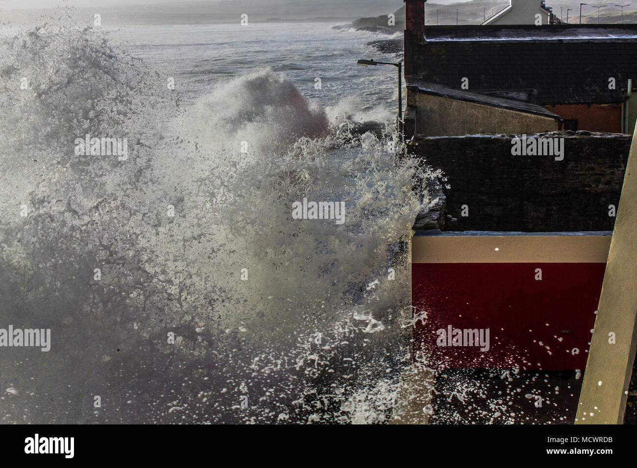 Wave coming over promenade and hitting buildings taken from above - Stock Image