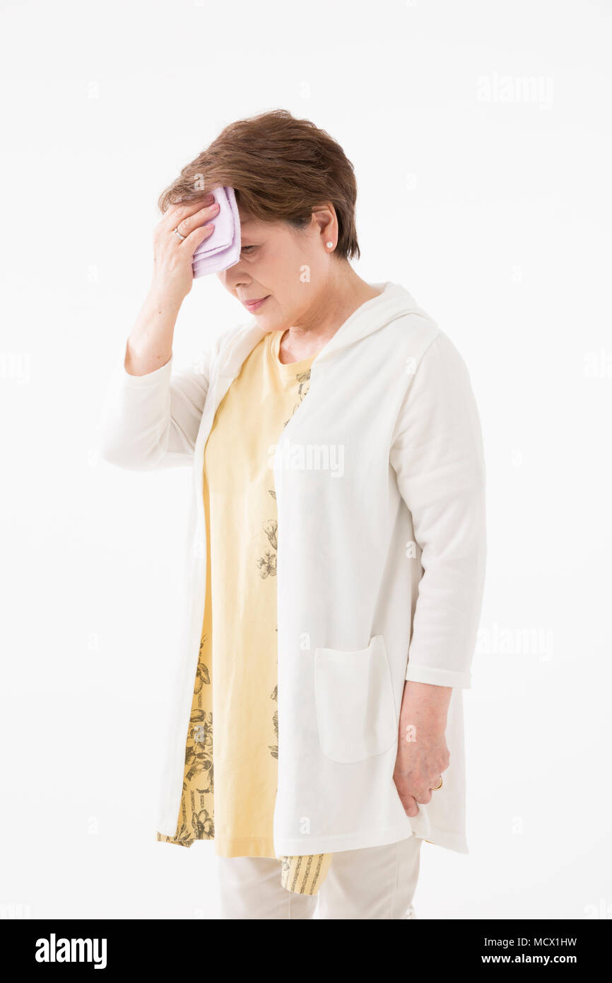 Senior woman wiping off sweat - Stock Image