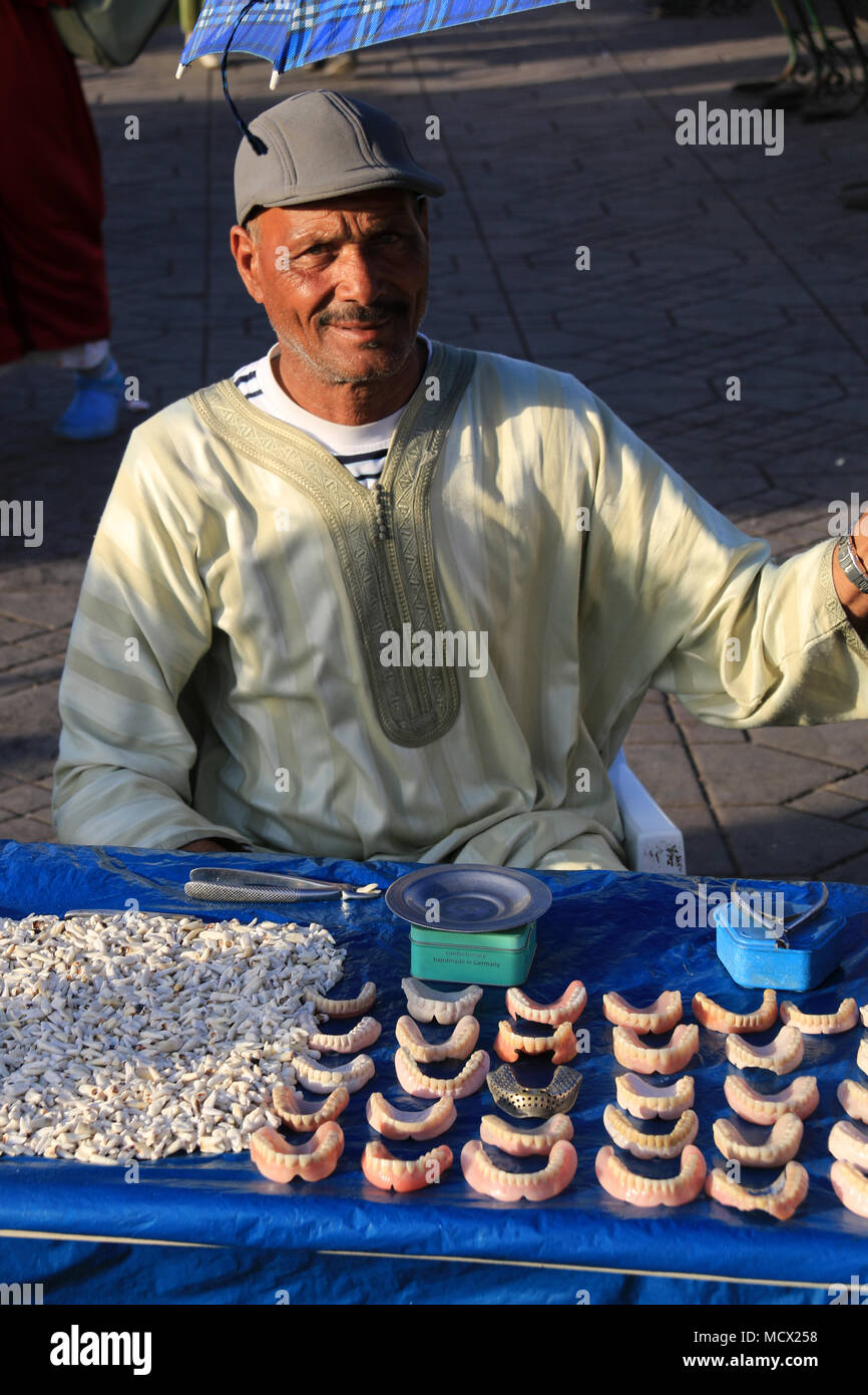 Moroccan senior selling used or new set of teeth at a market stall at the famous Jemaa el-Fnaa square in Marrakesh, Morocco Stock Photo