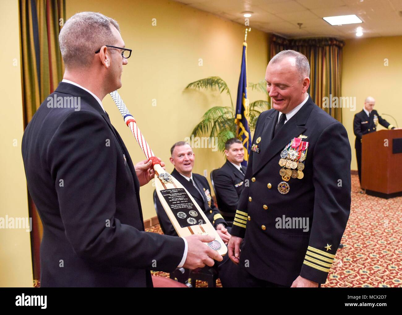 180223-N-YN937-106 VIRGINIA Beach, Va. (February 23, 2018) – Capt. Michael Sparks, commander, Navy Expeditionary Warfighting Development Center, (right) receives a gift from Senior Chief Utilitiesman Shawn Flynn during his change of command and retirement ceremony at Naval Air Station Oceana Dam Neck Annex. Navy Expeditionary Combat Command enables Navy Expeditionary Combat Forces to execute combat, combat support, and combat service support missions across the full spectrum of naval, joint, and combined operations which enable access for the sea and freedom of action throughout the sea-to-sho - Stock Image