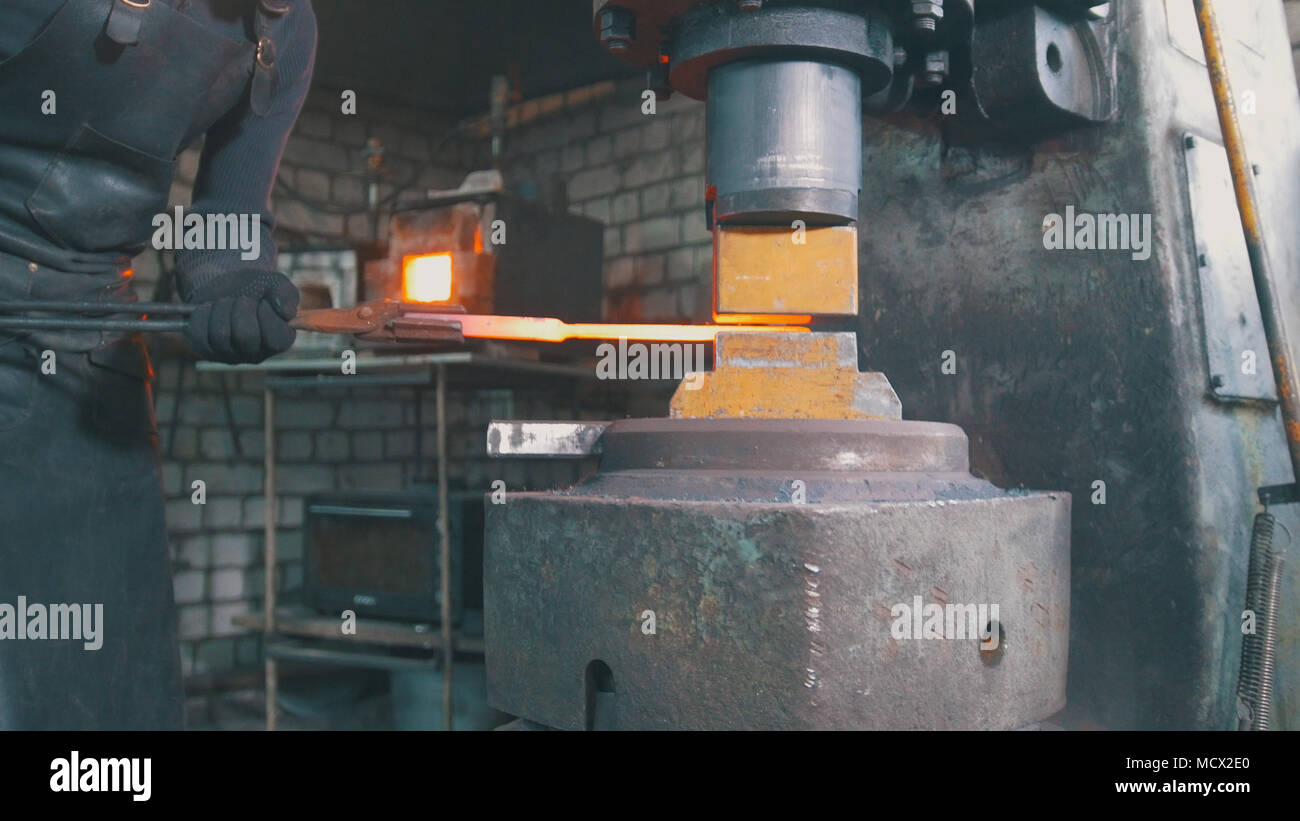 Automatic hammering - blacksmith forging red hot iron on anvil