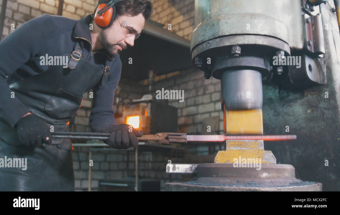 Blacksmith forging red hot iron on anvil - automatic hammering - Stock Image