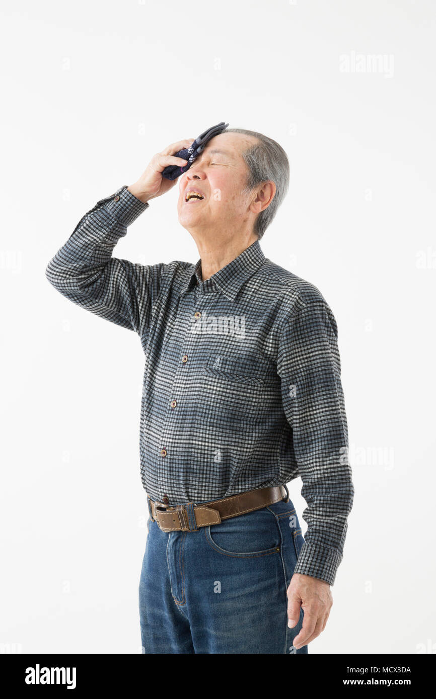 Senior man wiping off sweat - Stock Image