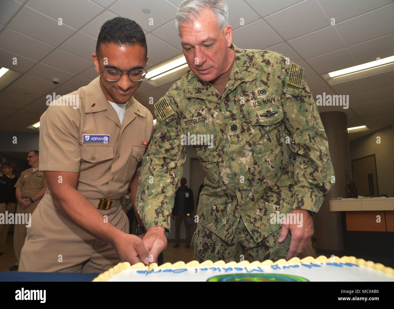 180302-N-PN275-1062 SAN DIEGO (March 02, 2018) End Vivek Abraham, left, and Cmdr Victor Ruttenbusch cut a cake as part of the 147th Medical Corps birthday celebration. Keeping with tradition the oldest and youngest Sailors cut the celebratory cake. (U.S. Navy Photo by Mass Communication Specialist 2nd Class Zach Kreitzer/Released) - Stock Image